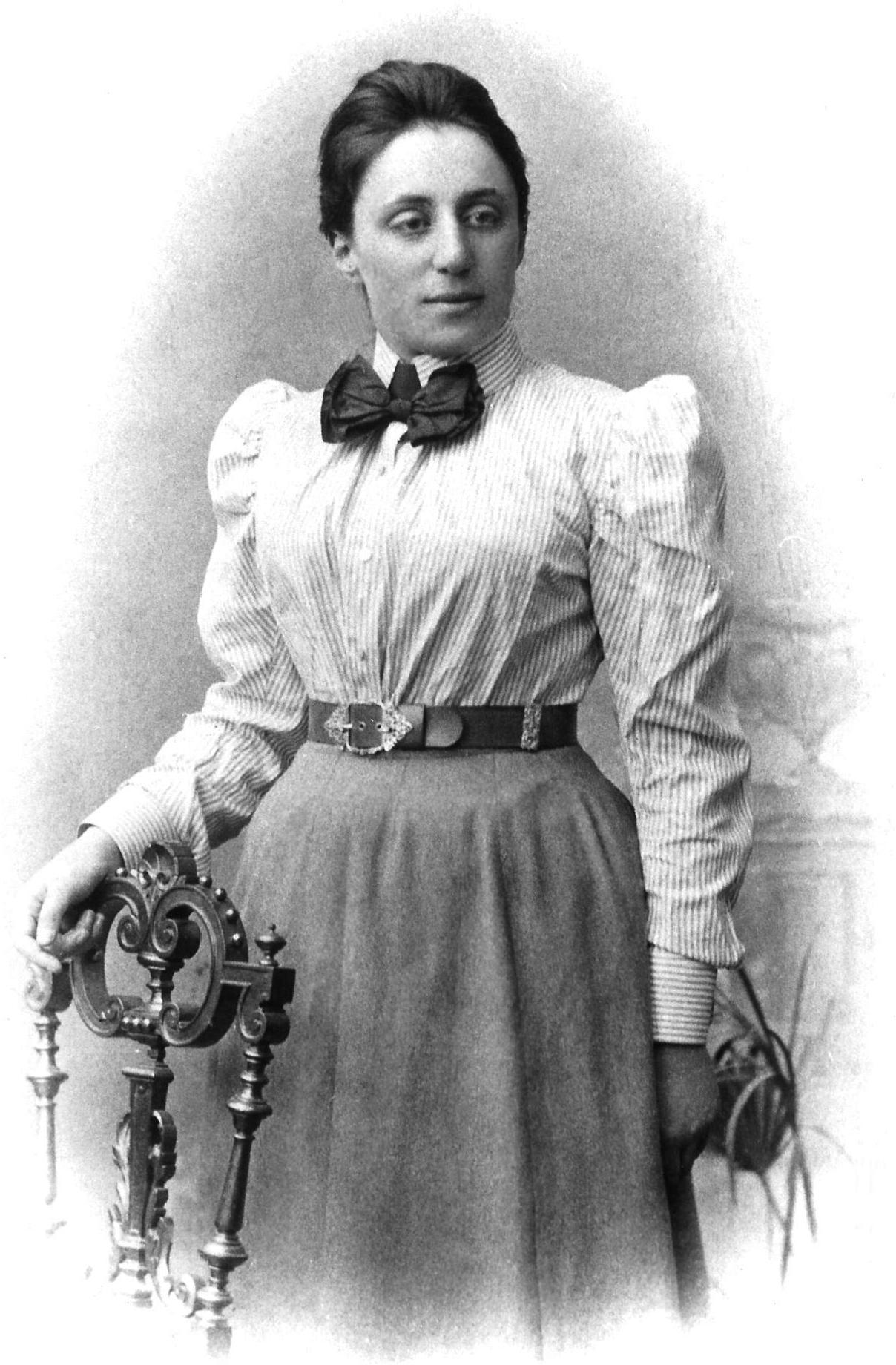 Fotografía de Emmy Noether de pie junto a una silla.